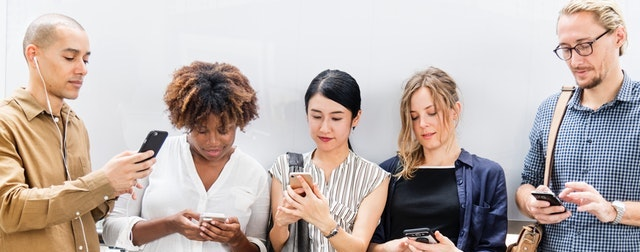 A group of people using mobile phones to access the dental phobia support forum