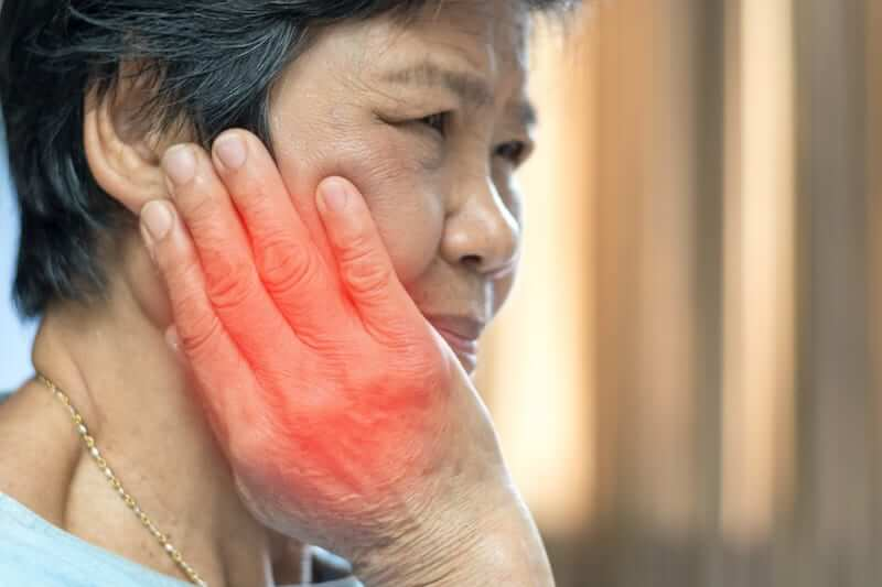 Woman with TMJ pain massaging her jaw joint