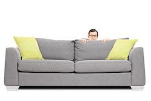 Fearful man hiding behind a sofa
